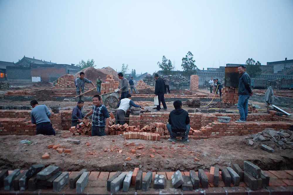 Workers builts the foundations of the temple with contemporain looking bricks which will be cover up by the traditional colours ones.