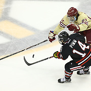 Braden Pimm #14 of the Northeastern Huskies and Quinn Smith #27 of the Boston College Eagles fight for the puck during The Beanpot Championship Game at TD Garden on February 10, 2014 in Boston, Massachusetts. (Photo by Elan Kawesch)