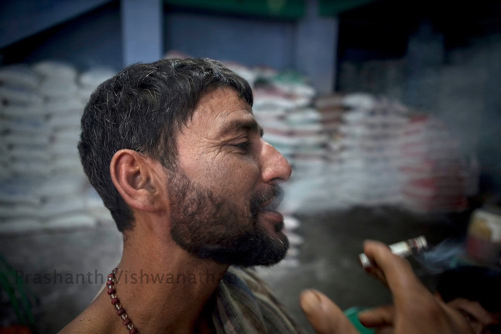 A labourer smokes a godown of a sugar distributor in the wholesale market of Old Delhi, in New Delhi, India, on Wednesday September 2, 2010. Photographer: Prashanth Vishwanathan/Bloomberg News