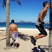 Fitness enthusiasts works out at fitness workstation on the edge of Copacobana Beach, Rio de Janeiro, Brazil. 6th July 2010. Photo Tim Clayton..The beaches of Rio de Janeiro, provide the ultimate playground for locals and tourists alike. Beach activity is in abundance as beach volley ball, football and a hybrid of the two, foot volley, are played day and night along the length and breadth of Rio's beaches. .Volleyball nets and football posts stretch along the cities coastline and are a hive of activity particularly at it's most famous beaches Copacabana and Ipanema. .The warm waters of the Atlantic Ocean provide the ideal conditions for a variety of water sports. Walkways along the edge of the beaches along with exercise stations and cycleways encourage sporting activity, even an outdoor gym is available at the Parque Do Arpoador overlooking the ocean. .On Sunday's the main roads along the beaches of Copacabana, Leblon and Ipanema are closed to traffic bringing out thousands of people of all ages to walk, run, jog, ride, skateboard and cycle more than 10 km of beachside roadway. .This sports mad city is about to become a worldwide sporting focus as they play host to the world's biggest sporting events with Brazil hosting the next Fifa World Cup in 2014 and Rio de Janeiro hosting the Olympic Games in 2016...
