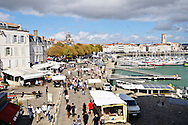 The bustling vieux port (old port) of La Rochelle, France is busy with locals and tourists on a sunny day.