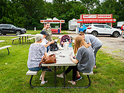 "26 JUNE 2020 - DES MOINES, IOWA: People from Des Moines set up their picnic table after ordering lunch at Fair Food Friday in Des Moines. The 2020 Iowa State Fair, like many state fairs in the Midwest, has been cancelled this year because of the COVID-19 (Coronavirus) pandemic. The cancellation of the fair left many small vendors stranded with no income. Some of the fair food vendors in Iowa started ""Fair Food Fridays"" on a property a few miles south of the State Fairgrounds. People drive up and don't leave their cars while vendors bring them the usual midway fare; corndogs, fried tenderloin sandwiches, turkey legs, deep fried Oreos, lemonaide and smoothies. Fair Food Friday has been very successful. The vendors serve 450-500 people per Friday and during the lunch rush people wait in line in their cars 30 - 45 minutes to place an order.     PHOTO BY JACK KURTZ"