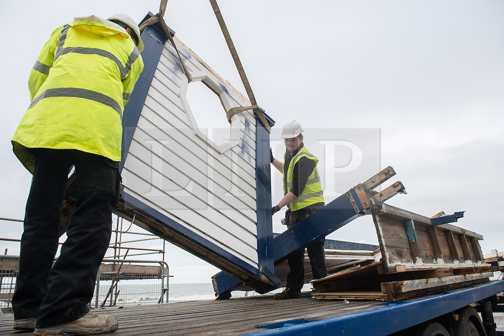 &copy; London News Pictures. Aberystwyth, UK. 22/01/2014.<br /> Workmen remove the last sections of the iconic 1920'€™s public shelter that was destroyed by the huge storms at Aberystwyth in early January 2014. The waves gouged out the hollow foundations underneath the Grade 2 listed building causing its collapse. The remains have now ben taken away for replacement and repair. Photo credit: Keith Morris/LNP<br /> <br /> <br /> photo &Acirc;&copy;keith morris