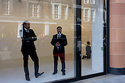 Art gallery staff stand in the window with a kneeling Hitler called La Fine di Dio by Maurizio Cattelan.