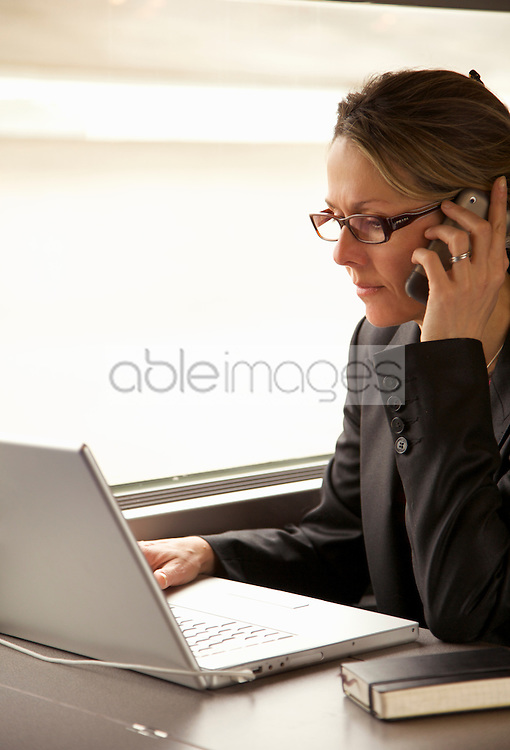 Woman on train using laptop computer and talking on cell phone