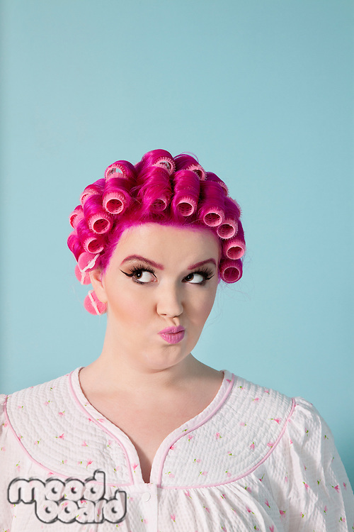 Young woman making faces with pink hair and curlers over colored background