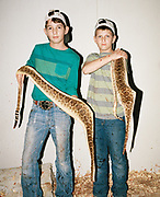 Cousins Josh Adames, 12, left, and Blake Trout, 10, right, both members of the Jay-teens, pose with the skins of snakes they just finished skinning.
