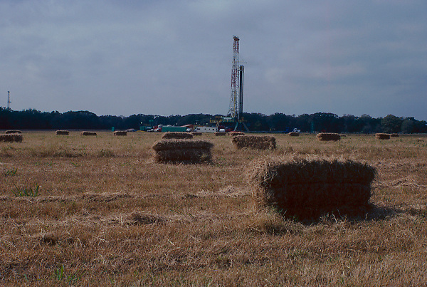 Stock photo of an on-shore rig beyond a farm's field of hay