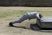 An older Japanese man performs press-ups in a park near Enoshima Aquarium, Enoshima, Kanagawa, Japan. Thursday March 5th 2020