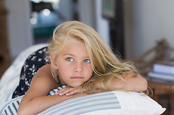 young blonde girl sitting on top of a couch in The Hamptons