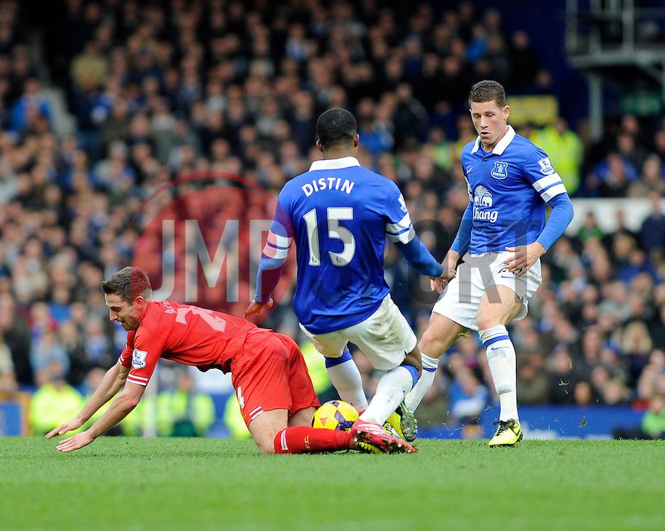 Everton's Sylvain Distin and Liverpool's Joe Allen get in a tangle - Photo mandatory by-line: Dougie Allward/JMP - Tel: Mobile: 07966 386802 23/11/2013 - SPORT - Football - Liverpool - Merseyside derby - Goodison Park - Everton v Liverpool - Barclays Premier League