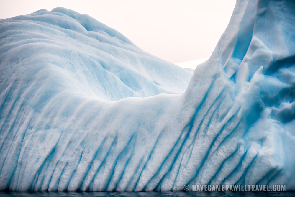 A blue iceberg with deep grooves gouged into the side from escaping compressed air pockets in Curtis Bay, Antarctica.