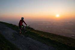 © Licensed to London News Pictures. 21/04/2019. Worcester, UK. A man cycles after a religious service at sunrise on Easter Sunday, at the Worcestershire Beacon. The Beacon is the highest point in the Malvern Hills at 425m. Easter Sunday is a key date in the Christian calendar. Photo credit : Tom Nicholson/LNP