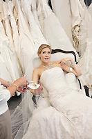 Tired young bride in wedding dress sitting while mother showing footwear