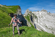 Hiker at Rotsteinpass (2120 m) in Switzerland, Europe. Behind, a transmission tower caps Säntis (2502 m), the highest mountain in the Alpstein massif of northeastern Switzerland, and highest of the Appenzell Alps. Appenzell Innerrhoden is Switzerland's most traditional and smallest-population canton (second smallest by area). For licensing options, please inquire.