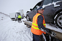 Tony Papetti, with A&J Towing, secures one of nine vehicles involved in four wrecks Wednesday near the Highway 41 exit in the westbound lanes of Interstate-90.
