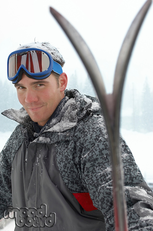 Young man wearing ski goggles on head holding skis in snow