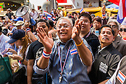 "20 DECEMBER 2013 - BANGKOK, THAILAND: SUTHEP THAUGSUBAN, leader of the anti-government protests, works the crowd during a march on Silom Road in Bangkok. Thousands of anti-government protestors, supporters of the so called Peoples Democratic Reform Committee (PRDC), jammed the Silom area, the ""Wall Street"" of Bangkok, Friday as a part of the ongoing protests against the caretaker government of Yingluck Shinawatra. Yingluck dissolved the Thai Parliament earlier this month and called for national elections on Feb. 2, 2014. The protestors want the elections postponed and the caretaker government to step down. The Thai election commission ruled Friday that the election would go on dispite the protests.          PHOTO BY JACK KURTZ"