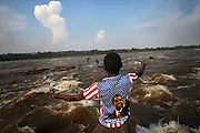 A fisherman gestures to men cast net fishing in the middle of the Lualaba River (Upper Congo River), 50km upstream from Kisangani on the Boyoma Falls, at Waina Rukula, DR Congo. The Boyoma Falls, also known as Wagenia Falls by the local tribe of the same name, consists of seven cataracts spread over 100km with the river dropping 60 meters and finishing at Kisangani.
