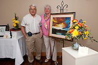 "Husband and wife team Tony and Carmel Lancia display their rendition of ""Evening Sunset at the Lancia's"" during Opechee Garden Club's Art 'N Bloom Thursday evening at Gilford Public Library.  (Karen Bobotas/for the Laconia Daily Sun)"