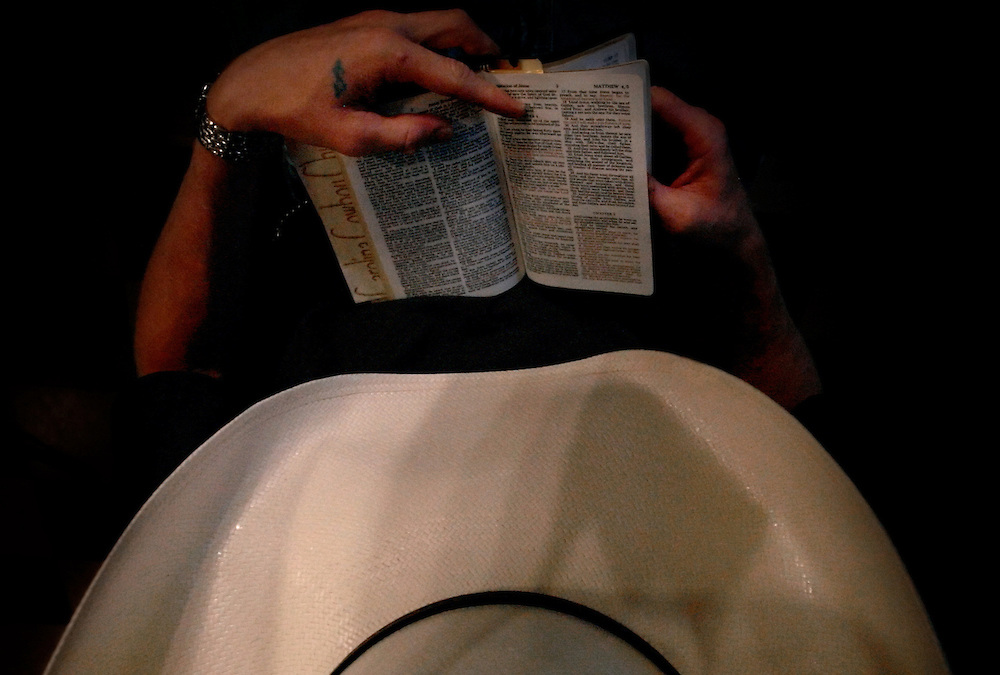 """Alex Rivenbark finds his place in the Bible during the Carolina Cowboy Church's reading. On his left hand between the index finger and thumb is a green tattoo of a dollar sign that Rivenbark gave himself when he was just 16 years old. """"I was greedy,"""" explained Rivenbark. Now 26 years old, Alex said he has turned from living a rough life to being saved by the Cowboy Church. """"I just felt God's pull on my heart,"""" Rivenbark said about his decision to start attending church again."""