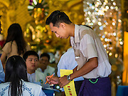 08 NOVEMBER 2015 - YANGON, MYANMAR:  A man gets his ballot in his polling place in a Buddhist temple in North Okkalapa, a township outside central Yangon. The citizens of Myanmar went to the polls Sunday to vote in the most democratic elections since 1990. The National League for Democracy, (NLD) the party of Aung San Suu Kyi is widely expected to get the most votes in the election, but it is not certain if they will get enough votes to secure an outright victory. The polls opened at 6AM. In Yangon, some voters started lining up at 4AM and lines were reported to long in many polling stations in Myanmar's largest city.     PHOTO BY JACK KURTZ