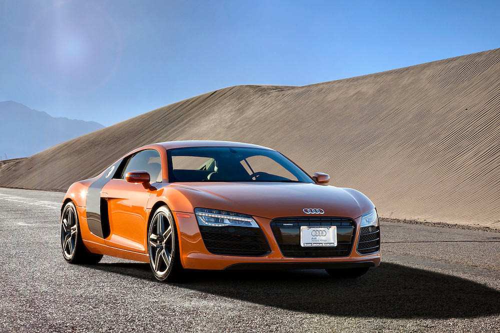 Photo of a Burnt orange 2012 Audi R8 on a desert road driving by sand Dunes.
