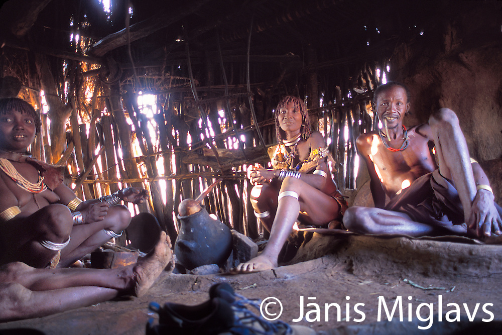 A Hamar (Hamer) tribe man with his wives chat with the photographer inside their house, Omo Valley, Ethiopia, Africa.