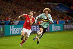 LILLE, FRANCE - Friday, July 1, 2016: Wales' Gareth Bale in action against Belgium's Marouane Fellaini during the UEFA Euro 2016 Championship Quarter-Final match at the Stade Pierre Mauroy. (Pic by David Rawcliffe/Propaganda)