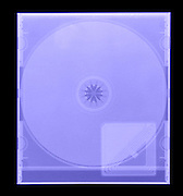 An X-ray of a CD and security device.  This is a compact disc (CD) that is used to store data or audio files.  To guard against theft, a security device in placed inside the package.  The security device is an antenna that  sets off an alarm is the device is not de-activated when a shopper leaves a store.  These inexpensive devices are used to guard against shoplifters and theft.