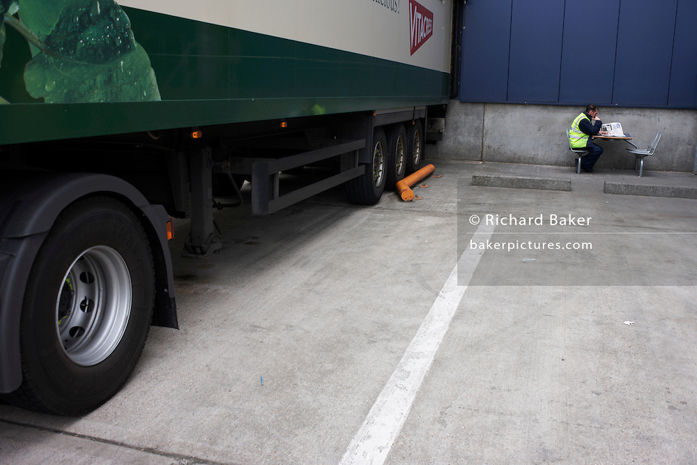 An HGV driver awaits his lorry to be loaded at Sainsbury's 700,000 sq ft (57,500sq m) supermarket distribution depot