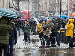 © Licensed to London News Pictures. 21/01/2018. London, UK. Tourists take photos on Whitehall during rainy and snowy weather. Photo credit : Tom Nicholson/LNP