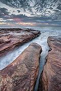 Water recedes through a rocky outcrop to the Indian ocean, Kalbarri, Australia