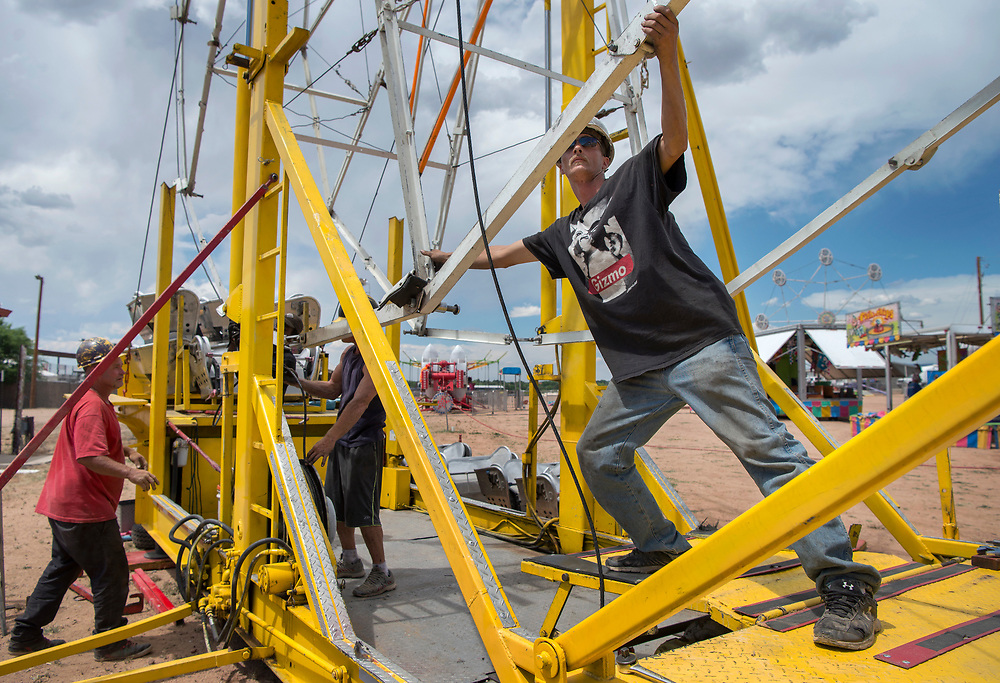em062017a/a/Kyle Good, right and others with A Great Northern A'Fair, attach a drive cable to a ferris wheel they are setting up at the Santa Fe Rodeo Grounds, Tuesday June 20, 2017. The fair opens Wednesday at 5 along with 68th Rodeo de Santa Fe. The fair and the rodeo run every evening through Saturday.  (Eddie Moore/Albuquerque Journal)