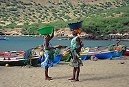 Two Cape verdean ladies chat on the beach at Tarrafal, Santiago, Cape Verde islands (Cabo verde).  Both wear brightly coloured clothing and are carrying baskets of freshly caught fish on their heads.  Tarrafal, or Villa de Tarrafal,  is a small fishing port on the north western tip of Santiago.  It has a beautiful sandy beach.  Brightly painted open wooden fishing boats and fishing nets are hauled up on to the sand.