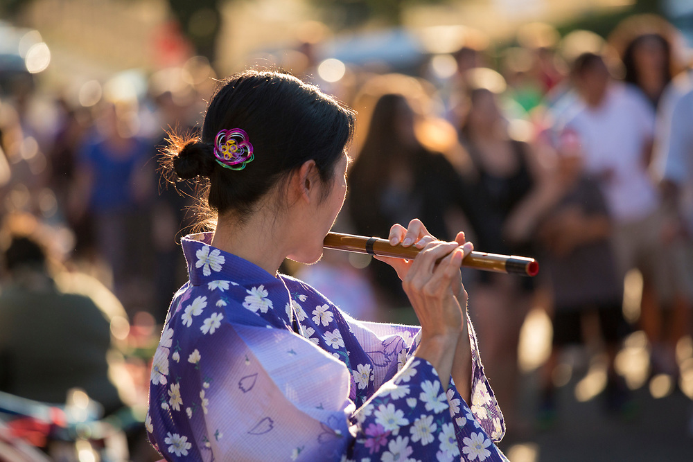 """United States, Washington, Seattle. Chinese New Year celebration in Seattle's """"International District"""", traditional home of the city's Asian community. Woman playing flute."""