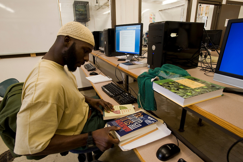 """Woodbourne Correctional Facility inmate and Bard College student Abdullah Kamau Sankofa studies in the computer room. He has been sentenced to 18 years in prison at the age of 17. He graduated from Bard College with fellow inmate Carlos Rosario in May 2010. (Book: The Future of Us All)..Story: The Bard Prison Initiative.Former inmate Carlos Rosario, 35-year-old husband and father of four, was released from Woodbourne Correctional Facility after serving more than 12 years for armed robbery. Rosado is one of the students participating in the Bard Prison Initiative, a privately-funded program that offers inmates at five New York State prisons the opportunity to work toward a college degree from Bard College. The program, which is the brainchild of alumnus Max Kenner, is competitive, accepting only 15 new students at each facility every other year. .Carlos Rosario received the Bachelor of Arts degree in social studies from the prestigious College Saturday, just a few days after his release. He had been working on it for the last six years. His senior thesis was titled """"The Diet of Punishment: Prison Food and Penal Practice in the Post-Rehabilitative Era,"""".Rosado is credited with developing a garden in one of the few green spaces inside the otherwise cement-heavy prison. In the two years since the garden's foundation, it has provided some of the only access the prison's 800 inmates have to fresh vegetables and fruit...Rosario now works for a recycling company in Poughkeepsie, N.Y...Photo © Stefan Falke"""