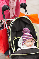 Mother walking with baby in stroller close up on baby