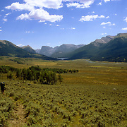 The headwaters of the Green River in the Wind River Range of Wyoming. Squaretop Mountain in the background. A solo backpacker walks toware a grove of trees.