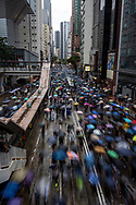 Despite a wet forecast,  hundreds of thousands of Hong Kongers — some estimates put the number as high as 1.7 million — made their presence felt at a protest rally centered in Victoria Park. The location was unable to hold the swelling numbers. In this photo, protestors walk down Hennessy Road.<br />