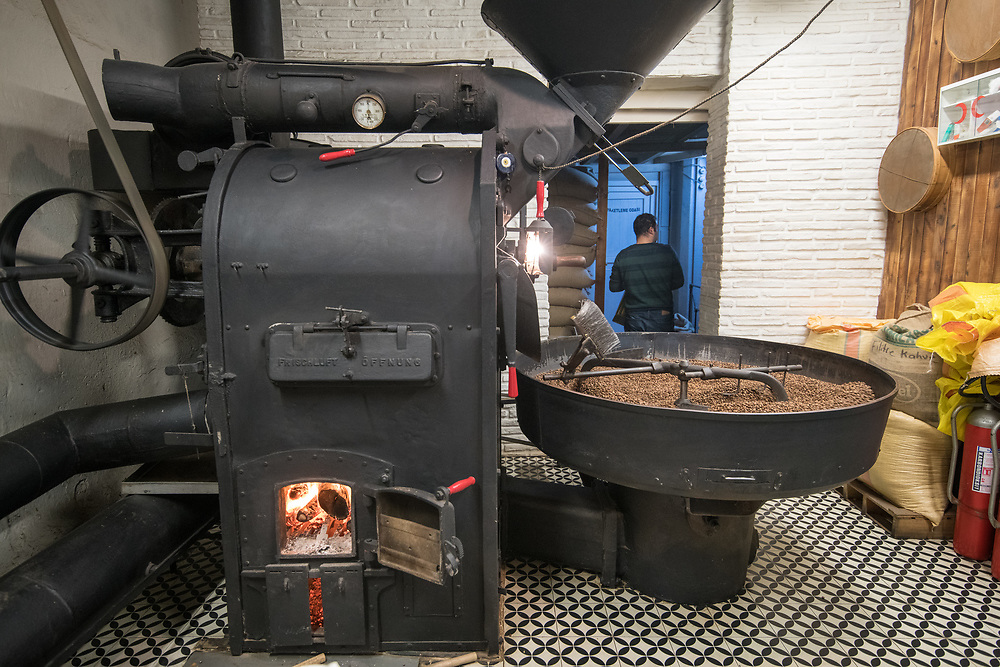 An industrial coffee bean roaster with a mechanical arm slowly rotating freshly roasted coffee beans to cool them down, Istanbul, Turkey.