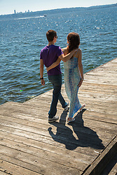 United States, Washington, Kirkland.  couple walking on pier on Lake Washington with boat and Seattle in distance.  MR