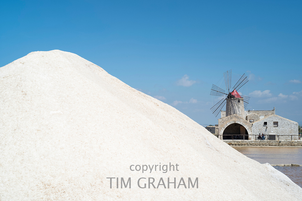 Mound of sea salt from salt pans at Saline di Trapani e Paceco and - behind - Museum of Salt and windmill at Nubia, Paceco, Sicily, Italy
