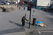 A woman reaches out to touch the pedestrian crossing sign at Elephant & Castle in Southwark, on 28th March 2019, in London, England