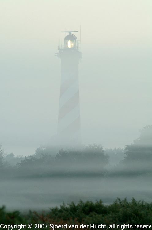 Lighthouse in fog near Burgh Haamstede, Zeeland, Netherlands.