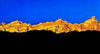 Surrealistic Triad: Three distinctive layers of colour and irregular shapes form a surrealistic sight; overlapping mountainous ridges are set against a blue sky to form irregular horizontal patterns at sunset, Capitol Reef National Park, Utah USA.