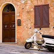 Vespa PX125E scooter parked next to home on street in Montepulciano, Tuscany, Italy