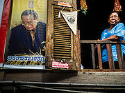 18 SEPTEMBER 2015 - BANGKOK, THAILAND: A woman in the in the window of her home near Wat Kalayanamit. A picture of Bhumibol Adulyadej, the King of Thailand, is on the wall of her home. She is being evicted from her home by the abbot at Wat Kalayanamit. Fiftyfour homes around Wat Kalayanamit, a historic Buddhist temple on the Chao Phraya River in the Thonburi section of Bangkok are being razed and the residents evicted to make way for new development at the temple. The abbot of the temple said he was evicting the residents, who have lived on the temple grounds for generations, because their homes are unsafe and because he wants to improve the temple grounds. The evictions are a part of a Bangkok trend, especially along the Chao Phraya River and BTS light rail lines. Low income people are being evicted from their long time homes to make way for urban renewal.             PHOTO BY JACK KURTZ
