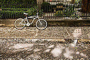 A bicycle park in front of a iron gate after a rain shower in Charleston, SC.
