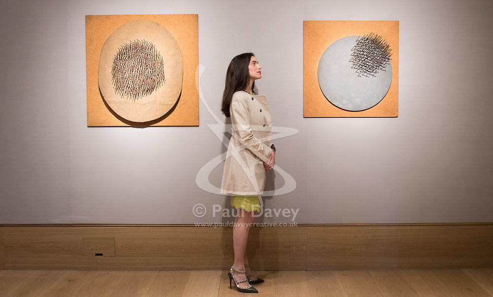 Bonhams, London, March 6th 2017. Fine art auctioneers Bonhams hold a preview in London  for their upcoming Post-War and Contemporary Art Sale which takes place on March 8th 2017. PICTURED: A woman examines Günther Uecker's 'Oval'  and 'Vogel', expected to fetch between £400,000 - 600,000.